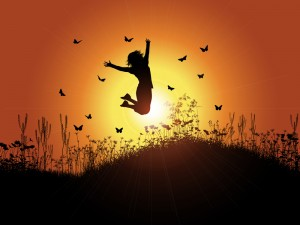 Silhouette of a woman jumping against a sunset background with g